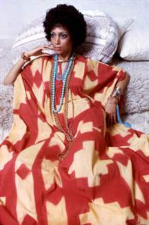 Portrait of an unidentified model, in a red and yellow print dress accented with gold and turquoise jewelry, as she poses on a set of neutral-colored throw pillows, New York, 1970s. (Photo by Anthony Barboza/Getty Images)