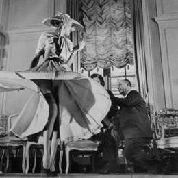 "11 Mar 1948, Paris, France --- Stockings were highlighted for the first time when Christian Dior (right), noted French designer, exhibited his French collection. The hose, which either continued the dress' color scheme from hem to ankles or afforded a direct contrast, ranged in shades from tender peach to ink black. The colors are called ""Boulevard Banquet."" Here a model swirls the skirt of a light blue crepe dress to feature the sheer navy blue stockings. --- Image by © Bettmann/CORBIS"